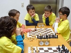 Alexander JANEK im Spiel mit Konstantin HALBEIS, gebannt verfolgt von anderen Kindern der Schachschule. Ergebnis: Remis