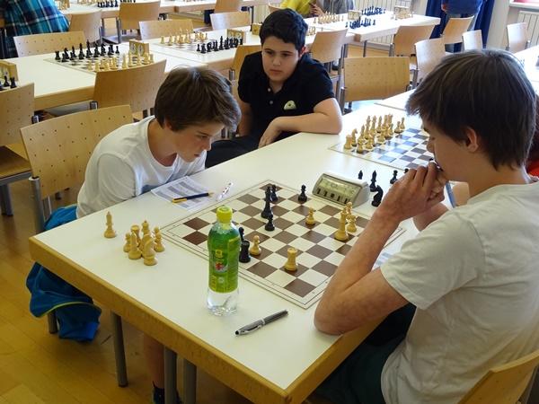 Laurin WISCHOUNIG (r.) gegen Andreas HIRZINGER (l.), genau betrachtet vom Mitkonkurrenten Gor TUMANYAN: Das Turmendspiel wäre trotz des schwarzen Freibauern auf d5 wahrscheinlich Remis.