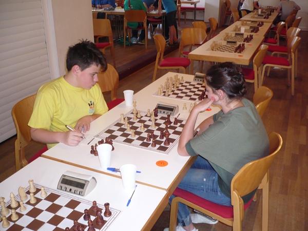 Victor NAT (li.) und Angelina ZHBANOVA (re.); trotz des Ungleichgewichts (Dame für Turm, Läufer und Bauer) steht Victor gut.