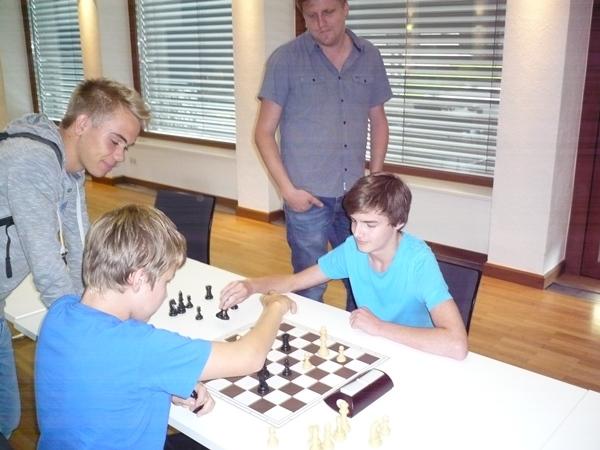 Laurin WISCHOUNIG (weiß) gegen Arthur KRUCKENHAUSER (schwarz). Links sieht Sebastian PELLIZZARI zu, dahinter Armin Baumgartner.